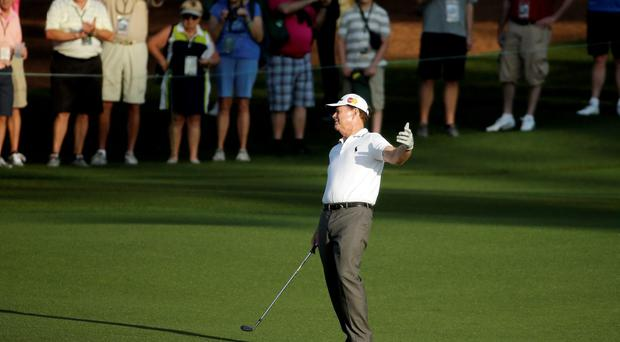 Tom Watson reacts to his shot on the second fairway during the first round of the Masters golf tournament