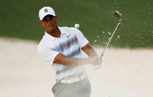 Tiger Woods of the U.S. hits from a sand trap onto the 10th green during first round play of the Masters golf tournament at the Augusta National Golf Course in Augusta, Georgia