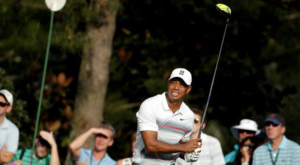 Tiger Woods watches his tee shot on the 14th hole during the first round of the Masters