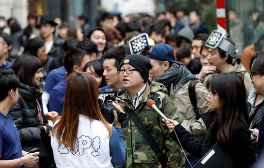 People wait for the going on display of Apple Watch in front of the Apple Store in Tokyo's Omotesando shopping district April 10, 2015. Apple Inc expects tremendous interest for its new smartwatch and demand to outstrip supply as consumers get an up-close look on Friday at CEO Tim Cook's first major product. REUTERS/Toru Hanai