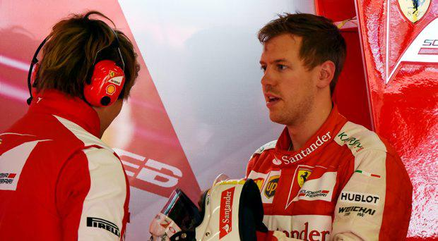 Ferrari's German driver Sebastian Vettel (R) speaks to a team member after the second practice session ahead of the Formula One Chinese Grand Prix in Shanghai on April 10, 2015