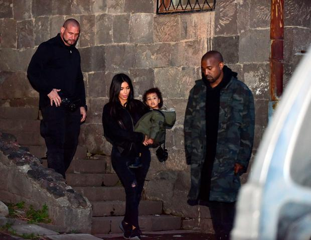 US reality TV star Kim Kardashian holds her daughter (C) in her arms next to her rapper husband Kanye West (R) as they walk close to the Geghard Monastery in Armenia