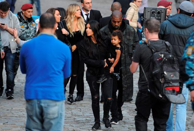US reality TV star Kim Kardashian holds her daughter North next to her rapper husband Kanye West