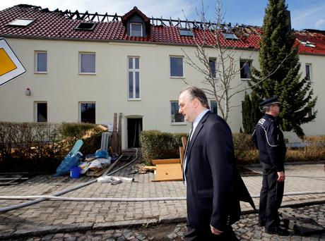 State Premier Reiner Haseloff of Saxony-Anhalt walks in front of a building damaged by a fire, which will be used as an asylum seekers home, in Troeglitz April 4, 2015. Authorities are investigating the cause of the fire which destroyed the roof, police said. REUTERS/Fabrizio Bensch