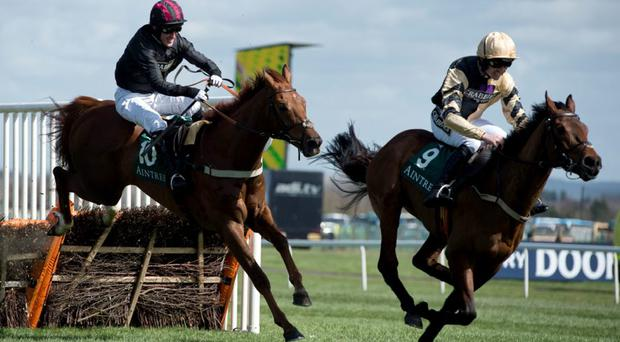 Jockey Ruby Walsh riding 'Nichols Canyon' (R) crosses the final fenceon the way to winning the Aintree Mersey Novices' Hurdle race ahead of Jockey A.P. McCoy riding 'Parlour Games' (L) on the final day of the Grand National Festival horse race meeting at Aintree Racecourse in Liverpool