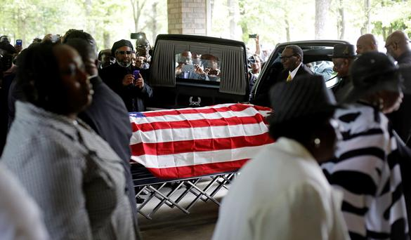 Mourners look on as the casket of Walter Scott is removed from a hearse for his funeral at W.O.R.D. Ministries Christian Center, Saturday, April 11, 2015, in Summerville. REUTERS/David Goldman/Pool