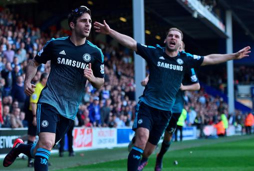 Cesc Fabregas celebrates with Branislav Ivanovic after scoring the winning goal against Queens Park Rangers at Loftus Road