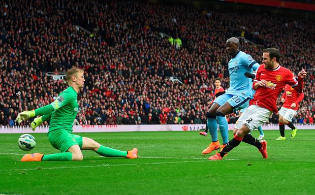 Juan Mata of Manchester United shoots past Joe Hart of Manchester City to score their third goal at Old Trafford