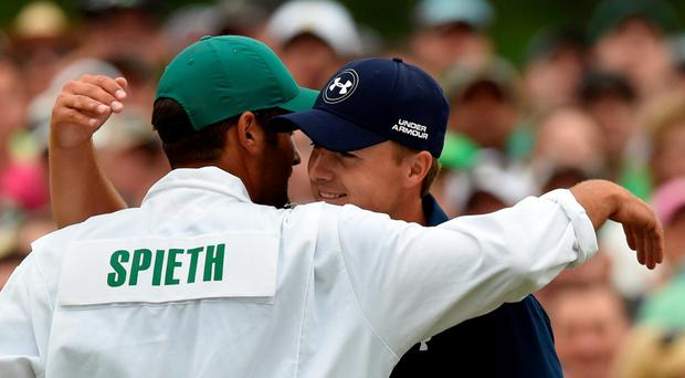 Jordan Spieth (R) of the US hugs caddie, Michael Greller, as he celebrates winning the 79th Masters