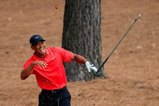 Tiger Woods reacts to a shot from the pine straw on the ninth hole during the final round of the 2015 Masters Tournament at Augusta National Golf Club