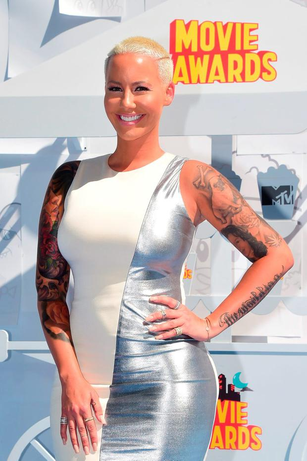 Model Amber Rose poses on arrival for the 2015 MTV Movie Awards