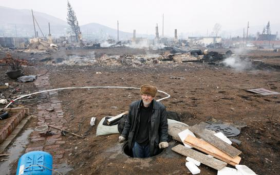 A man looks out from a manhole in the settlement of Shyra, damaged by recent wildfires, in Khakassia region