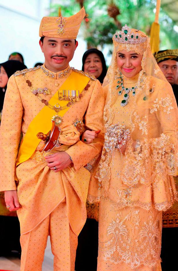 Brunei's newly wed royal couple, Prince Abdul Malik and Dayangku Raabi'atul 'Adawiyyah Pengiran Haji Bolkiah, pose for photographers after the