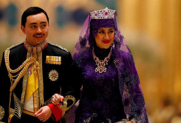 Brunei's newly wed royal couple, Prince Abdul Malik and Dayangku Raabi'atul 'Adawiyyah Pengiran Haji Bolkiah, leave the royal wedding banquet at the Nurul Iman Palace in Bandar Seri Begawan