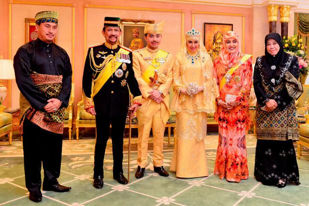 Brunei's newly wed royal couple, Prince Abdul Malik (3rd L) and Dayangku Raabi'atul 'Adawiyyah Pengiran Haji Bolkiah (3rd R), pose with Brunei's Sultan Hassanal Bolkiah (2nd L) and Queen Saleha (2nd R) and other members of Brunei's royal family, for photographers after the