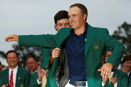 Defending champion Bubba Watson of the U.S. (rear) puts the traditional green jacket on compatriot Jordan Spieth after Spieth won the Masters golf tournament at the Augusta National Golf Course in Augusta, Georgia April 12, 2015. REUTERS/Jim Young