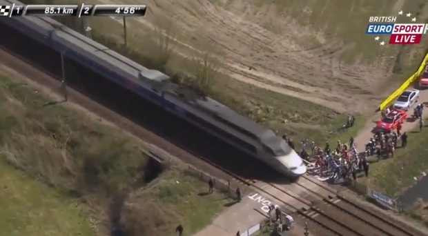 Riders wait to let a high-speed train pass during the Paris-Roubaix