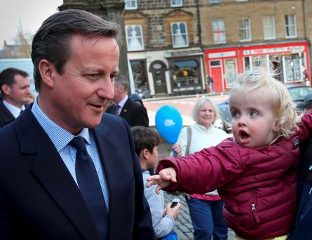 Britain's Prime Minister David Cameron talks with a local family as he campaigns in Alnwick. Photo: Reuters