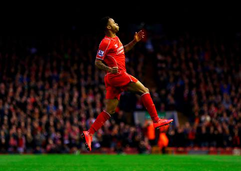 Raheem Sterling leaps with delight after opening the scoring for Liverpool at Anfield