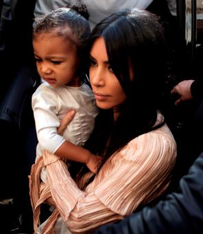 US reality TV star Kim Kardashian carries her daughter North West as she and her husband rapper Kanye West (back) exit a car upon their arrival at the Armenian St. James Cathedral in Jerusalem's Old City