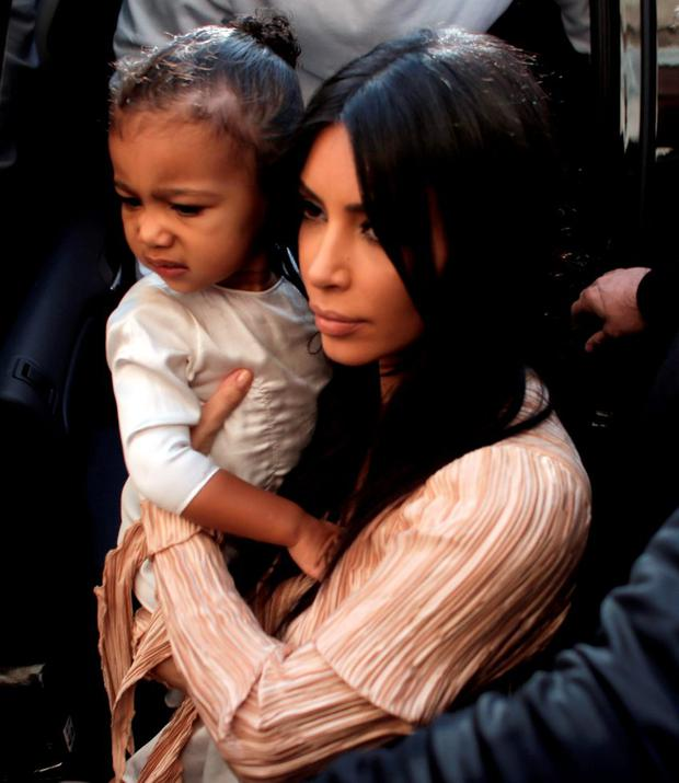 611effaaf259 US reality TV star Kim Kardashian carries her daughter North West as she  and her husband