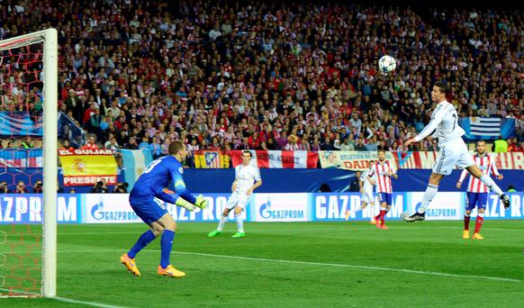 Real Madrid's Cristiano Ronaldo jumps to direct a header on the Atletico goal last night