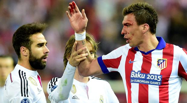 Atletico Madrid's Croatian forward Mario Mandzukic (right) argues with Real Madrid defender Dani Carvajal (left)