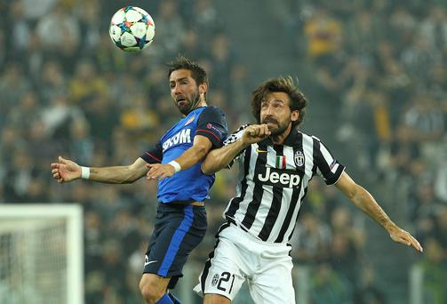 Monaco's Joao Moutinho competes in the air for the ball with Andrea Pirlo of Juventus