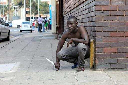 A foreign national holds a knife following clashes between a group of locals and police in Durban Credit: STRINGER/AFP