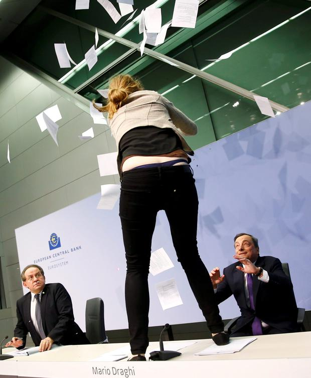 A protester jumps on the table in front of the European Central Bank President Mario Draghi during a news conference in Frankfurt, April 15, 2015. REUTERS/Kai Pfaffenbach