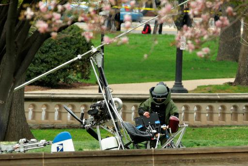 A member of the Bomb Squad works to check and secure a gyrocopter that landed outside the US Capitol