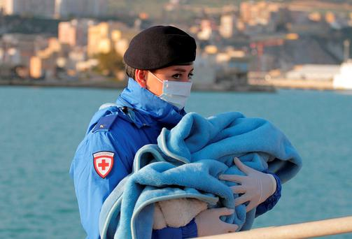 A Red Cross officer carries a baby wrapped in a blanket above, after migrants disembarked at the Sicilian Porto Empedocle harbour