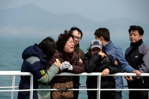 Relatives of victims of the sinking of the ferry Sewol weep as they stand on the deck of a boat during a visit to the site where the ferry sank off the coast of South Korea's southern island of Jindo Wednesday, April 15, 2015. (Ed Jones/Pool Photo via AP)