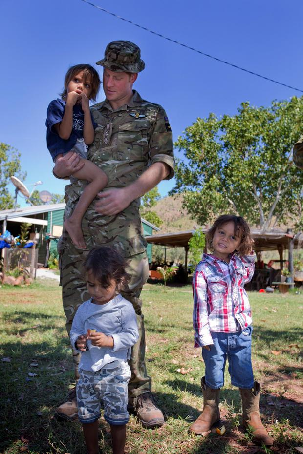 Prince Harry, known as Captain Wales in the British Army, plays with local children during a visit to the Wuggubun community, with members of the Australian Army's North-West Mobile Force (NORFORCE) in the Kununurra region of Western Australia, while on attachment with the Australian Army.