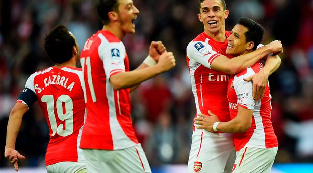 Alexis Sanchez of Arsenal (R) celebrates with Santi Cazorla (L), Mesut Oezil (2L) and Gabriel (2R) as he scores their second goal during the FA Cup Semi Final between Arsenal and Reading at Wembley Stadium on April 18, 2015 in London, England. (Photo by Mike Hewitt/Getty Images)