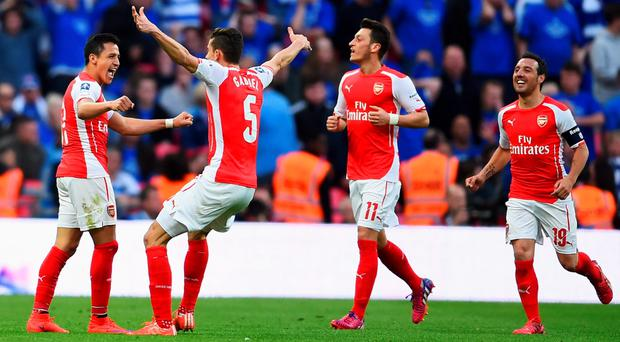 LONDON, ENGLAND - APRIL 18: Alexis Sanchez of Arsenal (L) celebrates with Santi Cazorla (R), Mesut Oezil (2R) and Gabriel (2L) as he scores their second goal during the FA Cup Semi Final between Arsenal and Reading at Wembley Stadium on April 18, 2015 in London, England. (Photo by Laurence Griffiths/Getty Images)