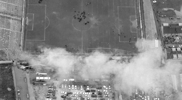 Aerial view of Bradford City's Valley Parade football ground with smoke rising from the devastating fire, which swept the main stand in four minutes just before half-time during the Division Three match against Lincoln City in the last game of the season. 56 people died and 265 were injured