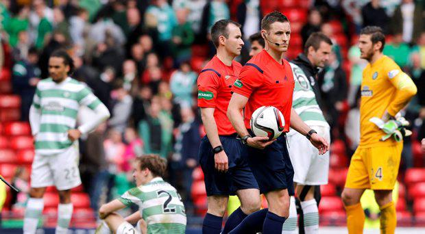 Referee Steven McLean walks off pitch at end of match as Celtic players look dejected