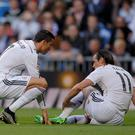 Real Madrid's Cristiano Ronaldo (left) tends to an injured Gareth Bale at the Santiago Bernabeu