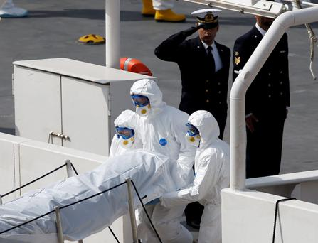An Italian coastguard officer salutes as Armed Forces of Malta personnel in protective clothing carry the body of a dead immigrant off the ship Bruno Gregoretti in Senglea, in Valletta's Grand Harbour REUTERS/Darrin Zammit Lupi