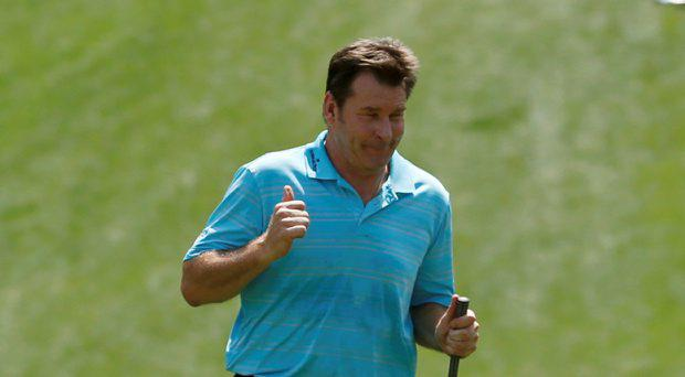 Nick Faldo of Britain dances after chipping in on the first hole during the par 3 event held ahead of the 2015 Masters at Augusta National Golf Course in Augusta