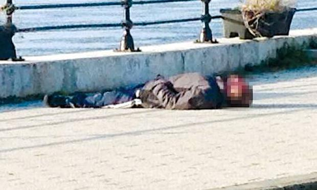 Graham Warke's photograph of an unidentified homeless man, lying unconscious beside the River Foyle. The image has become a talking point after being posted on Facebook