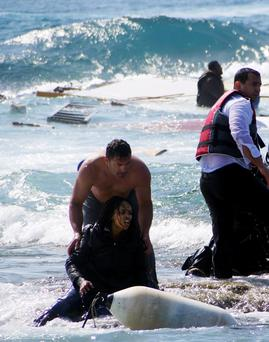 A migrant, trying to reach Greece, is rescued by a man at the coast of the southeastern island of Rhodes April 20, 2015. REUTERS/Argiris Mantikos/Eurokinissi