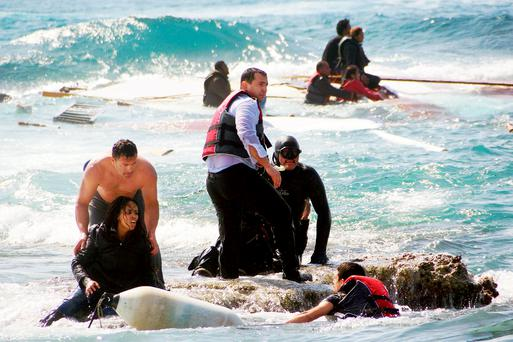 A man rescues an migrant from the Aegean sea, in the eastern island of Rhodes. Greek authorities said that at least three people have died, including a child, after a wooden boat carrying tens of migrants ran aground off the island of Rhodes. Photo: AP
