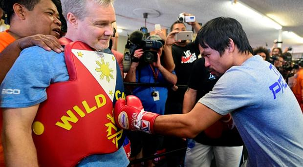 Boxer Manny Pacquiao spars with his coach Freddy Roach