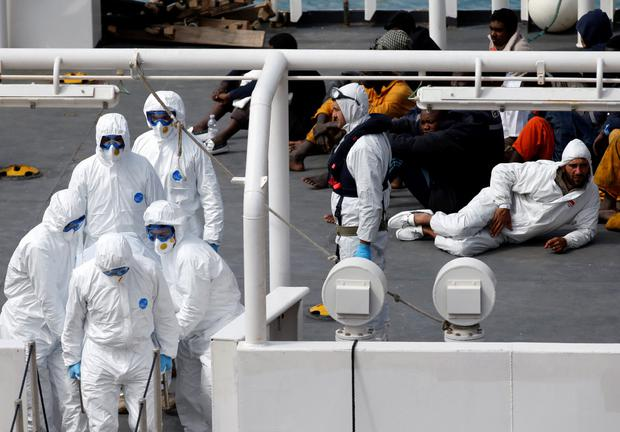 Mohammed Ali Malek (R, in white), one of two survivors of Saturday's migrant boat disaster, later arrested on suspicion of people trafficking, is seen watching bodies of dead migrants being disembarked from the Italian coastguard ship Bruno Gregoretti in Senglea in Valletta's Grand Harbour April 20, 2015