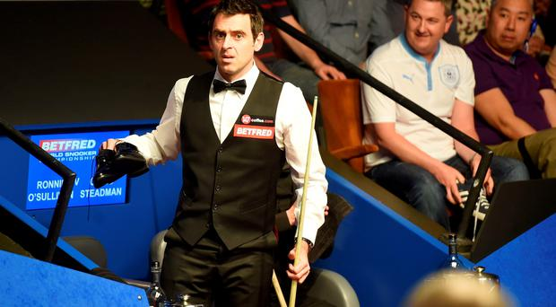 Ronnie O'Sullivan talks with referee Brendan Moore about his shoes his after he played in his socks against Craig Steadman, during the Betfred World Championships at the Crucible Theatre,