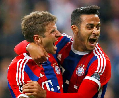 Thomas Muller celebrates scoring Bayern Munich's fourth goal with Thiago Alcantara at the Allianz Arena last night
