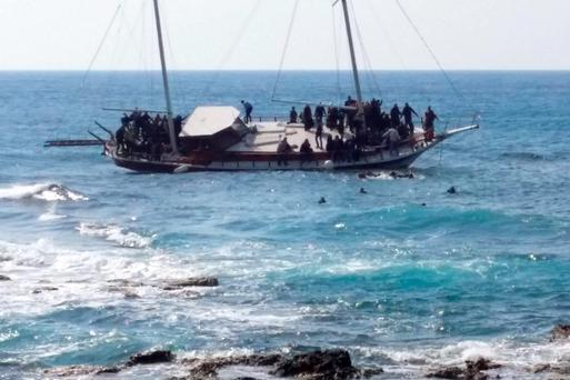 Migrants swim to reach the shore as others remain on a listing vessel, which later sunk off the Greek island of Rhodes on Monday with the loss of three lives