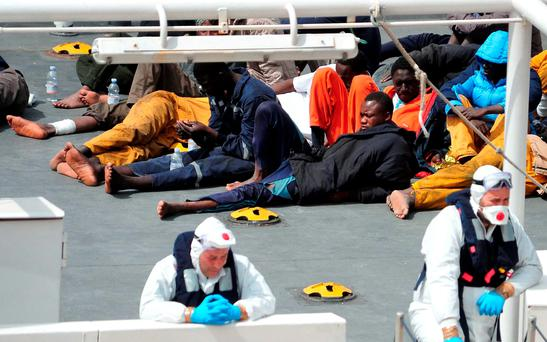 Survivors of the smuggler's boat that overturned off the coasts of Libya lie on the deck of the Italian Coast Guard ship Bruno Gregoretti, in Valletta's Grand Harbour. Photo: AP